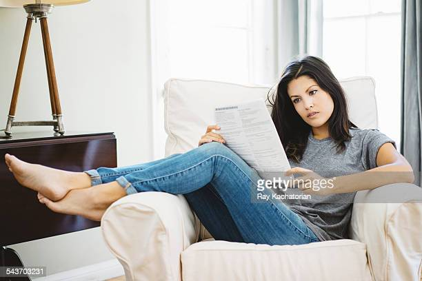 Woman sitting on couch reading letter