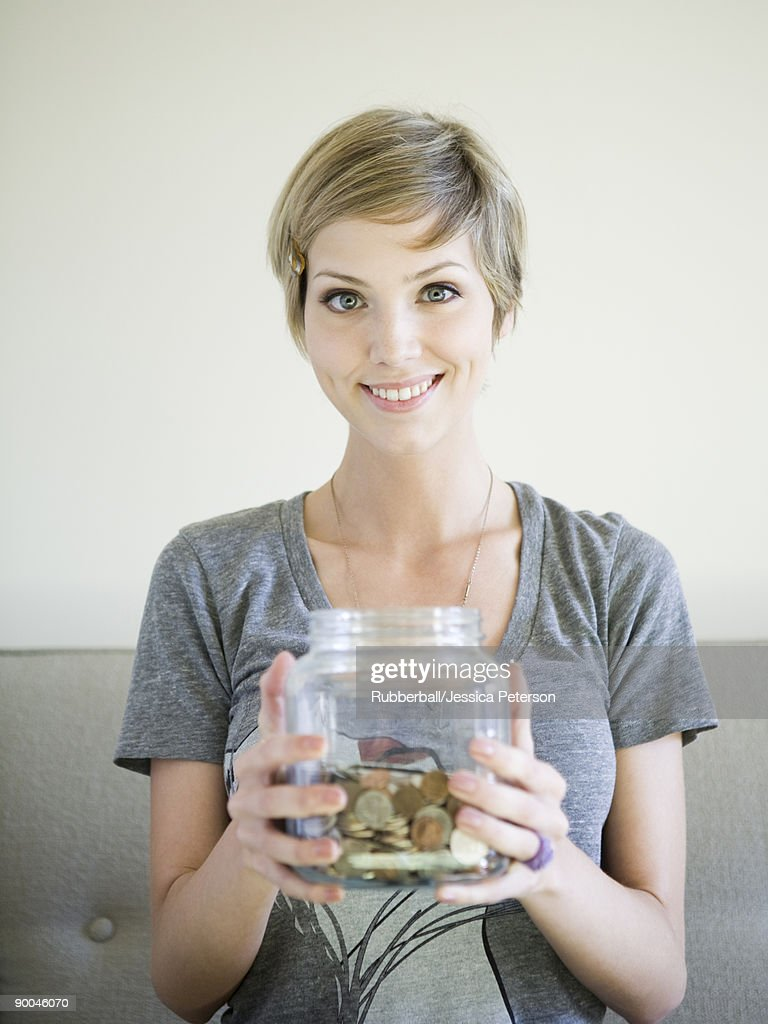 woman sitting on couch with a jar of coins : Stock Photo