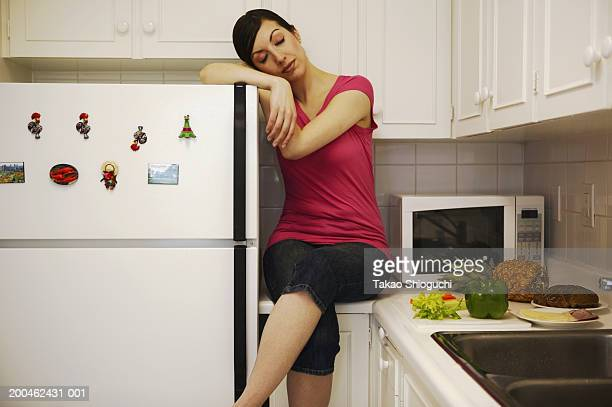 Woman sitting on countertop, resting head on refrigerator, eyes closed