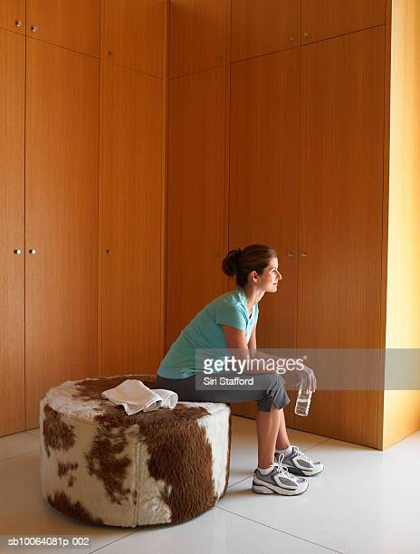 Woman sitting on cow print chair, side view