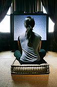 Woman sitting on cushion, watching static on television, rear view