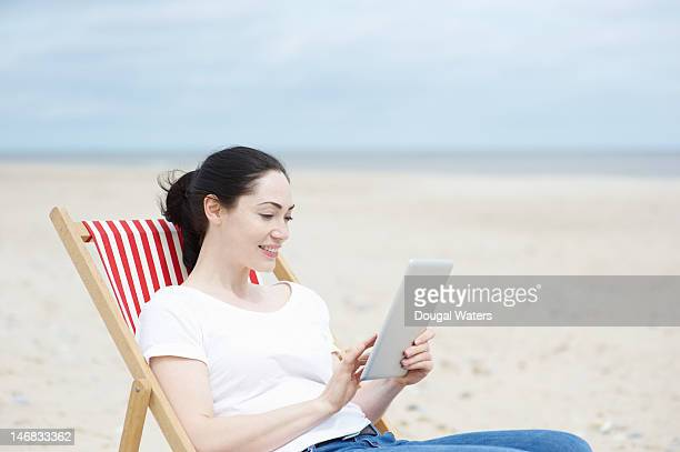 Woman sitting on deck chair at beach with tablet.