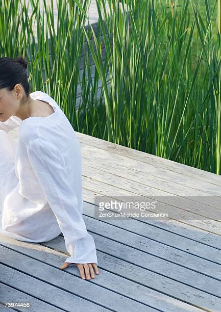 Woman sitting on deck, partial view