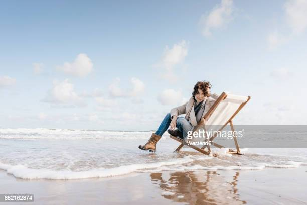 Woman sitting on deckchair on the beach