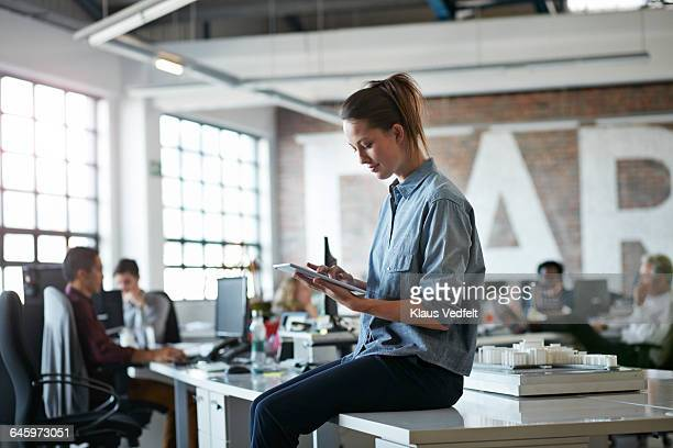 Woman sitting on desk with tablet at, open office