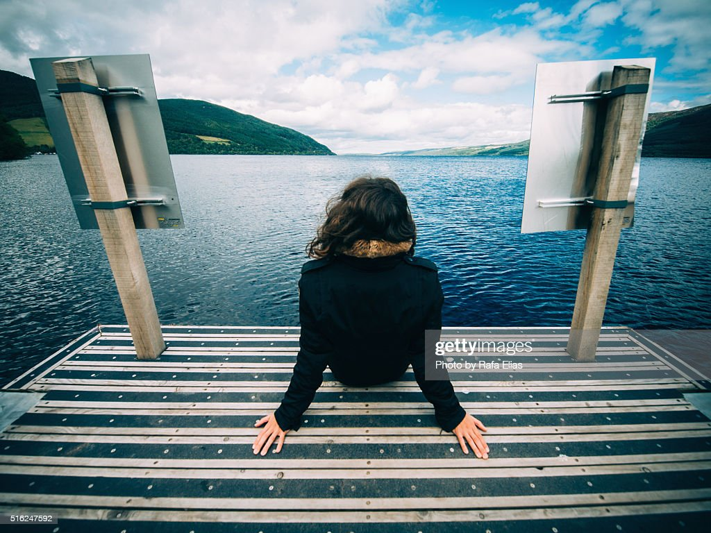 Woman sitting on dock in front of Loch Ness (Scotland)