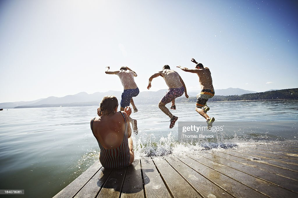 Woman sitting on dock while men jump into water : Stock Photo