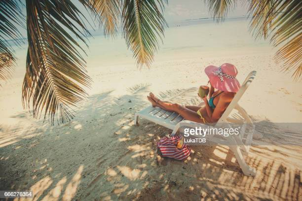 Woman sitting on easy chair on the beach, Maldives