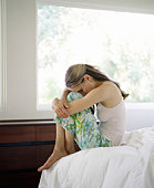 Woman sitting on edge of bed, resting head on legs, side view
