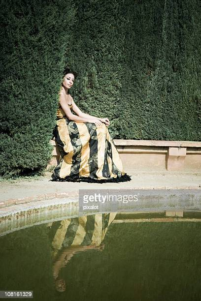 Woman Sitting on Edge of Garden Pond