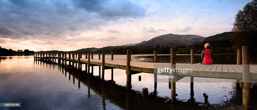 Woman Sitting on Edge of Lake Dock at Sunset : Stock Photo