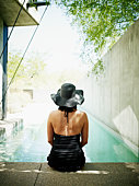 Woman sitting on edge of pool rear view