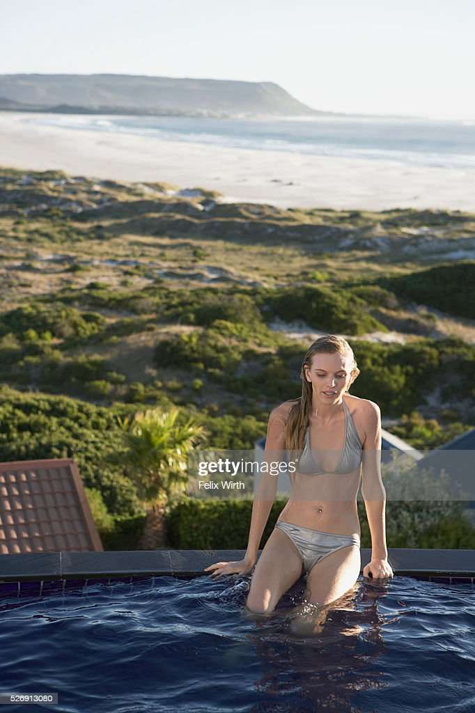 Woman sitting on edge of swimming pool : Stockfoto