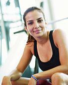 Woman sitting on exercise machine in gym, portrait, close-up