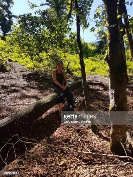 Woman Sitting On Fallen Tree At Forest