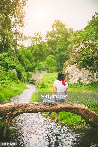 Woman sitting on fallen tree trunk over the river