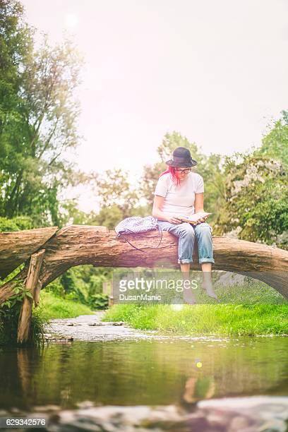 fallen femme assise sur le tronc d'arbre sur la rivière