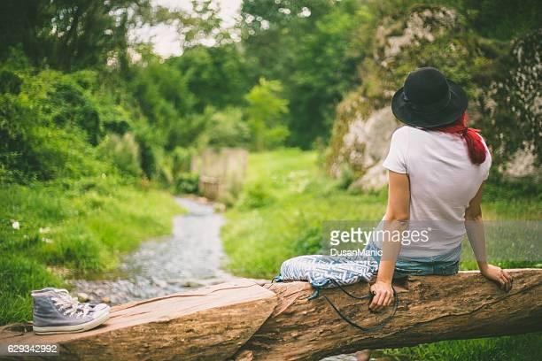 座っている女性に落ちた木の幹、川