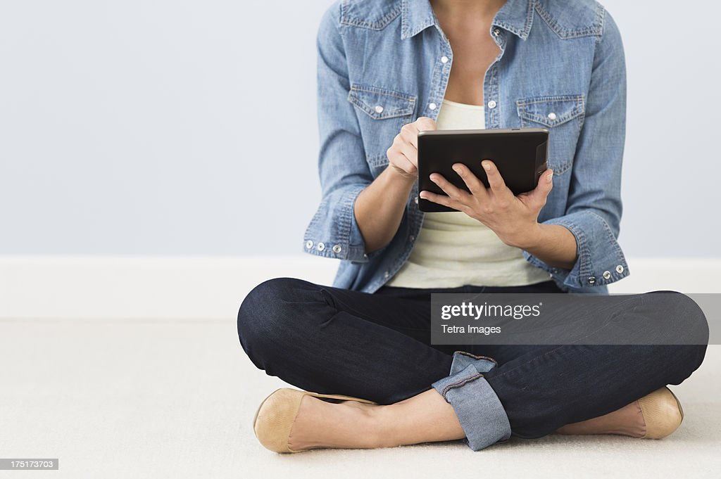 Woman sitting on floor and using digital tablet : Stock Photo