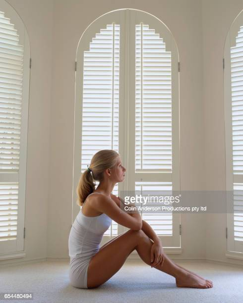 Woman Sitting on Floor by Windows