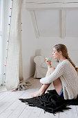 Woman sitting on floor drinking tea