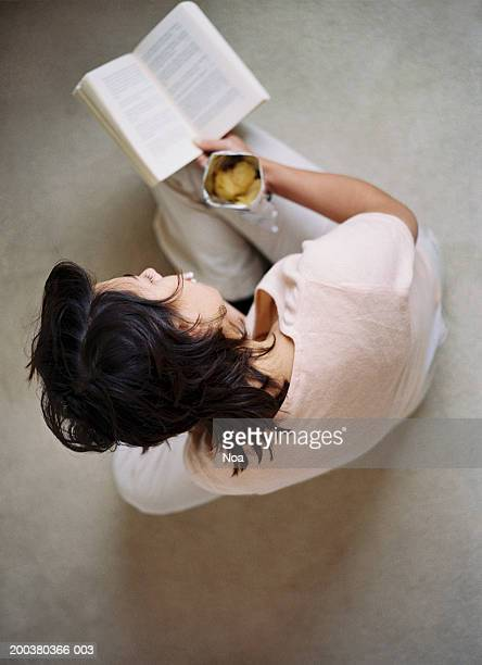 Woman sitting on floor holding bag of crisps, reading, overhead view