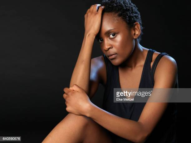 woman sitting on floor in sports outfit looking defeated