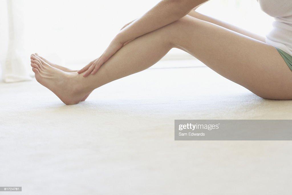 Woman sitting on floor indoors relaxing : Stock Photo