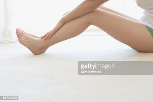 Woman sitting on floor indoors relaxing : Stock Photo