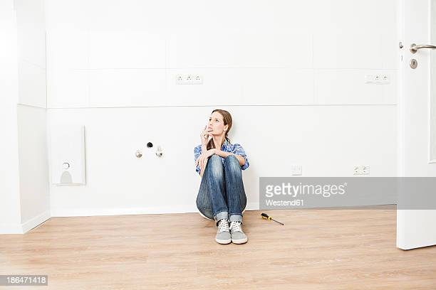 Woman sitting on floor, looking away