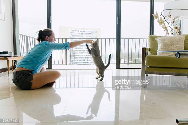 Woman sitting on floor plying with cat, side view