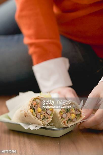 Woman sitting on floor with burritos