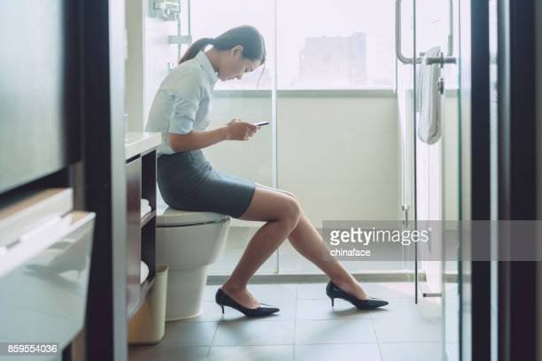 woman sitting on flush toilet typing smartphone