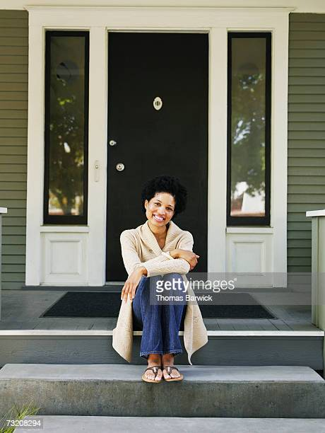 Woman sitting on front doorstep of home, portrait