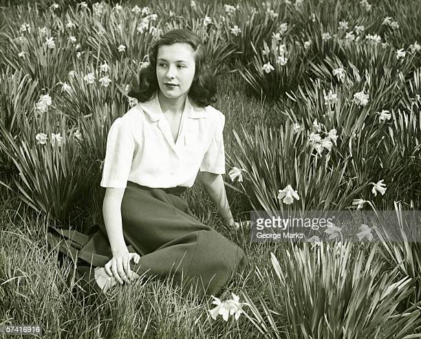Woman sitting on grass among blooming daffodils, (B&W), (Portrait)