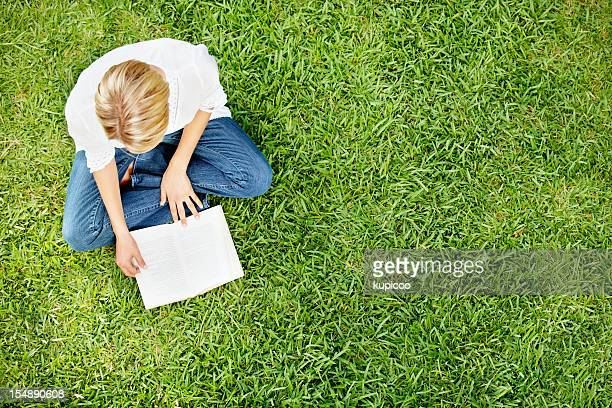 Woman sitting on green grass and reading book