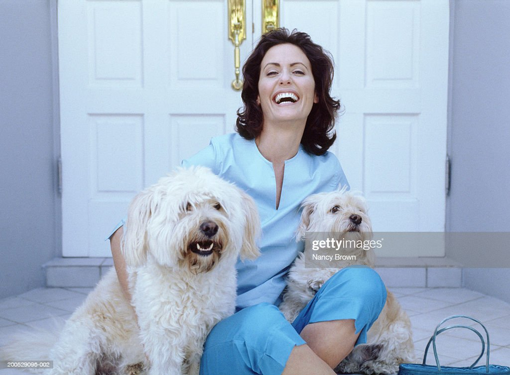 Woman sitting on ground, embracing two dogs, smiling, portrait : Stock Photo