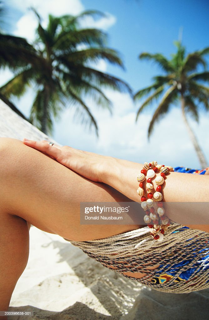 Woman sitting on hammock on beach, low section, close-up : Stock Photo