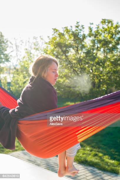 Woman sitting on hammock  outdoors on a chilly spring morning