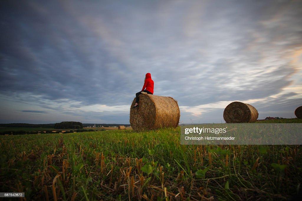 Woman sitting on hay bale