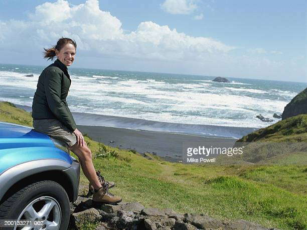 Woman sitting on hood of car, beach in background