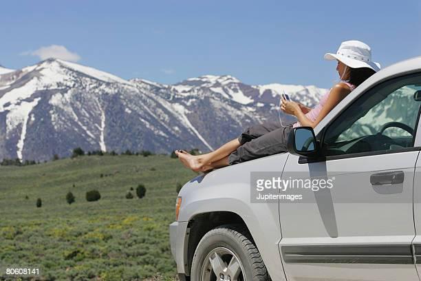 Woman sitting on hood of car, Mammoth Lakes area, California