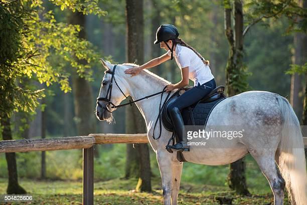 Frau sitzt auf Pferd