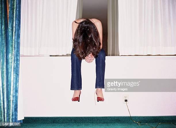 Woman sitting on hotel room windowsill, head bowed