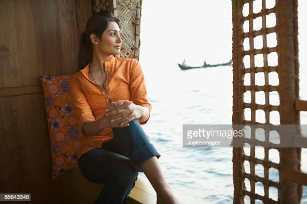Woman sitting on houseboat, India