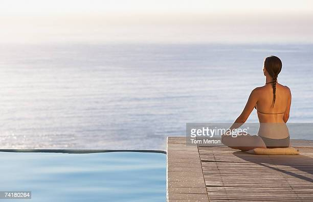 Woman sitting on infinity pool deck doing yoga rear view