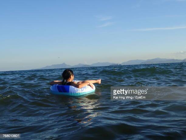 Woman Sitting On Inflatable Ring In Sea Against Clear Sky