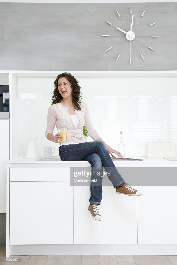 Woman sitting on kitchenette : Stock Photo