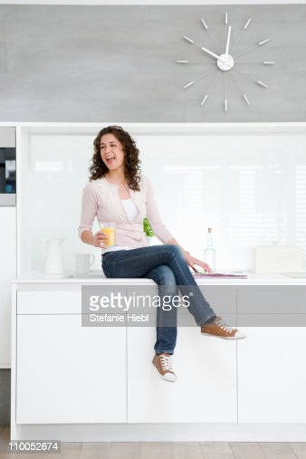 Woman sitting on kitchenette : Stock Photo
