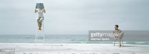 Woman sitting on ladder on beach, reading, man watching her